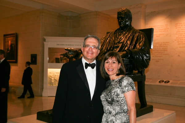 Alumni at the Supreme Court gala pose in front of a statue