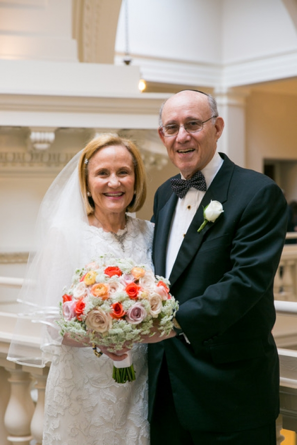 Carol Mates in a wedding dress holding a bouquet and Mark Kahan in a tuxedo