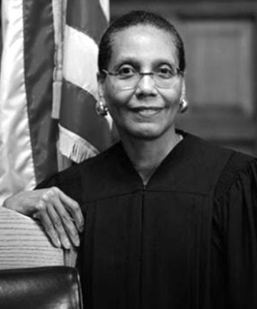 Judge Sheila Abdus-Salaam BAR '74, LAW '77 stands in front of an American flag.