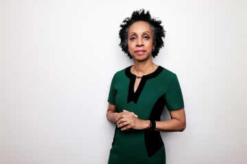 Portrait of Nina Shaw in a green and black dress