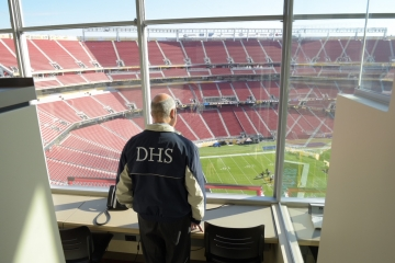 Man in DHS jacket looks over empty football stadium