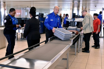 Man in blue uniform at airport security checkpoint